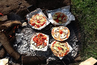 pizzas cooking on open fire