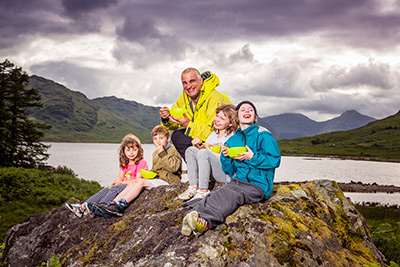 Tim and kids sitting on a rock eating hills and loch Arklet behind