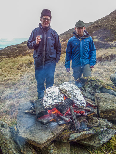 two men in front of a small cooking fire on a windy day