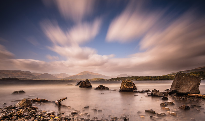 low down view of rocks by Loch Lomond clouds streaking by